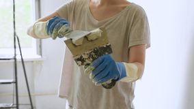 Young female worker preparing putty for the wall repair stock footage