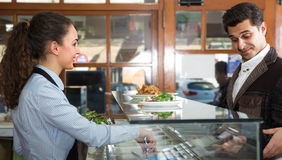 Young female worker serving customer with smile. At shawarma place Stock Image