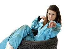 Young female worker sitting in a car tire Stock Images