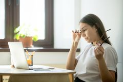 Tired businesswoman holding glasses and rubbing eyes in home off. Young female worker with tired eyes holding glasses. Woman feeling discomfort from long wearing royalty free stock photos