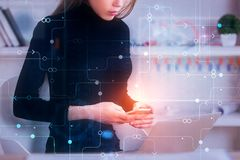 Media and tech concept. Young female worker using glowing smartphone at office workplace with laptop and digital business hologram. Media and tech concept Royalty Free Stock Photography
