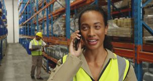 Young female worker using smartphone in a warehouse stock video footage
