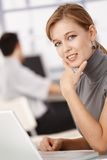 Young female working on laptop in office smiling Stock Images