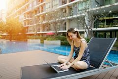 Young woman working with laptop pc outdoors remotely as freelancer close to swimming pool and apartment building. Young female working with laptop pc computer Royalty Free Stock Photography