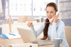 Young female working on laptop talking on phone Stock Photo