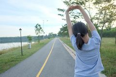 Young female workout before fitness training session at the park. She is stretching her arm royalty free stock photo