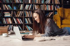 Young woman writer in library at home creative occupation lying writing book on laptop. Young female writer in library indoors working lying on the carpet typing Royalty Free Stock Photography