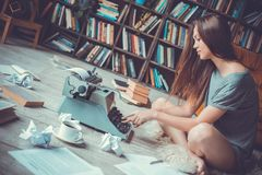 Young woman writer in library at home creative occupation pressing buttons royalty free stock image