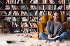 Young woman writer in library at home creative occupation sitting writing notes. Young female writer in library indoors working sitting on the carpet taking stock photos