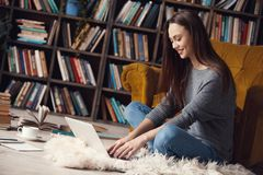 Young woman writer in library at home creative occupation sitting typing on laptop. Young female writer in library indoors working sitting on the carpet working Stock Photos