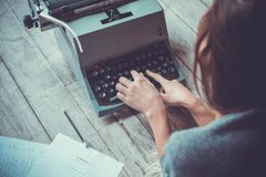 Young woman writer in library at home creative occupation typing typewriter. Young female writer in library indoors working typing on typewriter back view close royalty free stock image
