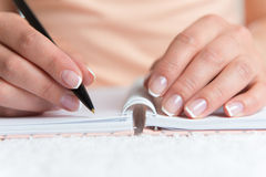 Young female is writing notes Stock Images