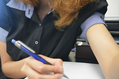 Young female writing on paper. An office caption of a young female writing on paper and dressed in office clothing stock image