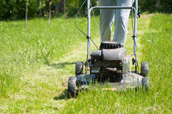 Young female in yard - pushing grass trimming lawnmower Royalty Free Stock Photo