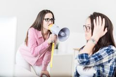 Young female yelling through megaphone at her coworker stock image