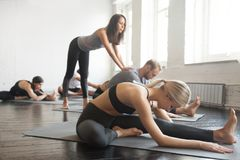 Young female yoga instructor teaching Janu Sirsasana pose for gr. Young female yoga instructor teaching Janu Sirsasana pose, Head to Knee Forward Bend exercise Royalty Free Stock Images