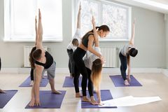 Young female yoga instructor teaching Utthita Trikonasana pose. Extended triangle exercise for a group of sporty people practicing in studio, working out Stock Photo
