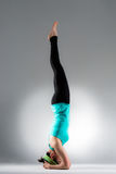 Young female yoga student handstand on floor Stock Photos