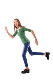Young female youth rushing forwards and waving one hand in studi Royalty Free Stock Photos