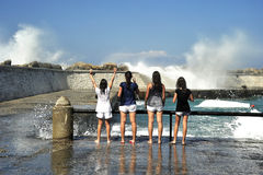 Young females have fun with waves Royalty Free Stock Photo