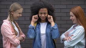 Young females mocking black classmate, bullying victim closing ears, conflict. Stock footage stock footage