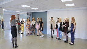 Young females are preparing for defile in model school. Teacher is controlling order of beautiful women walking up and down getting ready for fashion show stock video footage
