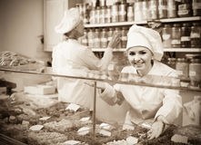 Young females staff offering nuts. In shop Stock Photo