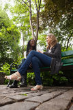 Young females talking to each other in park Royalty Free Stock Photo