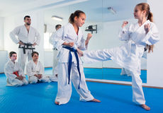 Young females are trying in sparring to use new moves. At karate class Stock Images