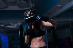 Young fighter boxer fit girl in VR glasses wearing boxing gloves Stock Photography