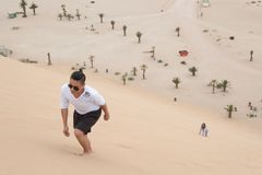 Young Filipino climbs Dune 7, Walvis Bay, Namibia. A young Filipino climbs Dune 7, the highest sand dune in the world, in Walvis Bay, Namibia Stock Photography