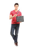 Young filmmaker holding a movie-clapper. Full length portrait of a young filmmaker holding a movie-clapper isolated on white background Royalty Free Stock Photos