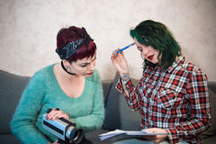 Young filmmaker women collaborating working at home. Couple of young filmmaker women sitting at home collaborating working and about movie idea, pen paper and Stock Photos