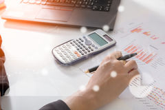 Young finance market analyst working at sunny office on laptop while sitting at white table.Businessman analyze document. And the calculator in hands.Graphs and stock photo