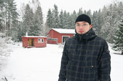 Young finnish man and traditional finnish cottage Royalty Free Stock Photos