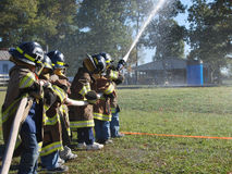 Young fire fighters. Young children dressed in fire fighting gear with fire hose trying to spray water in a barrel Stock Photo