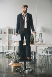 Young fired businessman standing on chair and trying to hang himself Royalty Free Stock Images