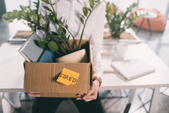 Young fired businesswoman holding box with belongings Stock Photos
