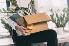 Young fired businesswoman holding box with belongings Royalty Free Stock Photography