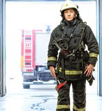 Young firefighter against truck Stock Photo