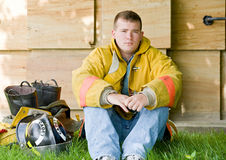 Young Fireman. Sitting in the Grass Royalty Free Stock Photo