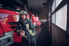Young fireman wearing protective uniform standing next to a fire engine in a garage of a fire department royalty free stock images
