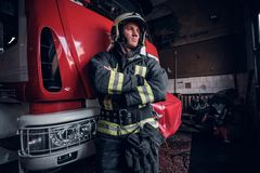 Young fireman wearing protective uniform standing next to a fire engine in a garage of a fire department. Portrait of a brave young fireman wearing protective royalty free stock photos