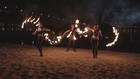 Young fireshow artists juggling flame near river stock footage
