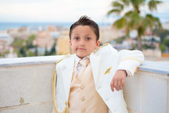 Young First Communion boy leaning on a wall with his elbow. Young boy with white suit leaning on a wall with his elbow in his First Communion Stock Images