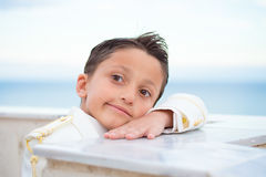Young First Communion boy leaning on a wall with his head over h Stock Image