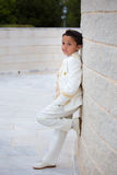 Young First Communion boy leaning on a wall with  one foot Stock Photo