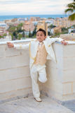 Young First Communion boy leaning on a wall Stock Photo