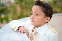 Young First Communion boy leaning on a wall. Young boy with white suit leaning on a wall in his First Communion. Shallow depth of field Stock Photos