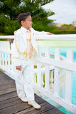 Young First Communion boy leaning on a white wooden fence over a Stock Photo